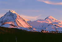 69ORCAC_05 - USA, Oregon, Three Sisters Wilderness, Sunset light on North (left) and Middle Sister (right) with autumn snow above conifers and lava flow, near McKenzie Pass.