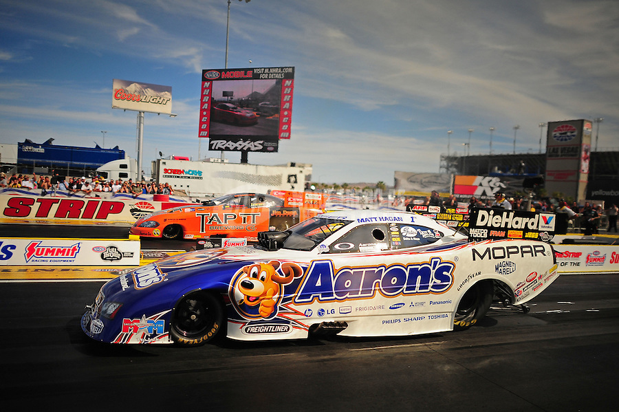 Mar. 30, 2012; Las Vegas, NV, USA: NHRA funny car driver Matt Hagan (near) races alongside Todd Lesenko during qualifying for the Summitracing.com Nationals at The Strip in Las Vegas. Mandatory Credit: Mark J. Rebilas-US PRESSWIRE
