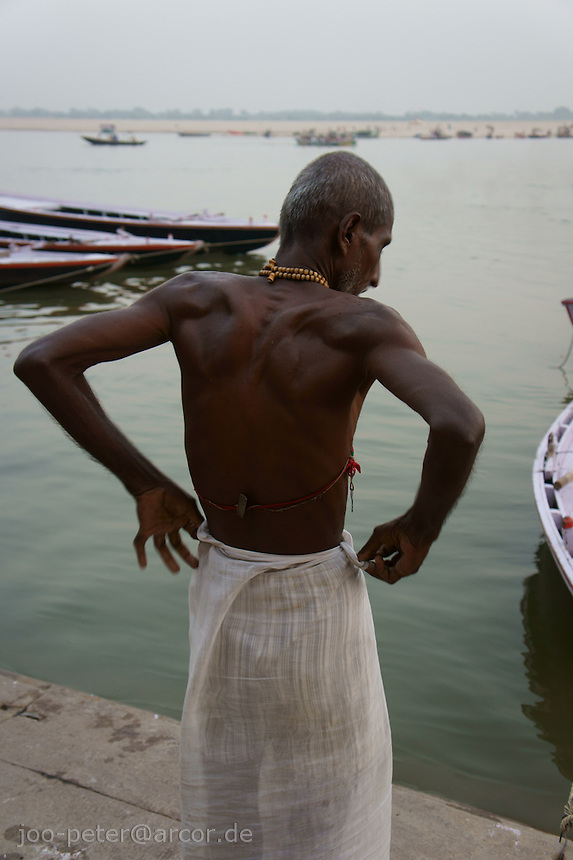 Devoted worshipper dressing after bath in holy river Ganga in Varanasi