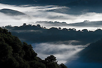 Early morning fog hangs in the low lands below Los Laureles Grade between Carmel Valley and the Salinas Valley - Coastal Mountain Range, California.