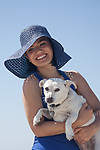 Young brunette woman with  blue hair at the beach with her white dog