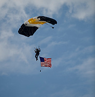 ELMONT, NY - JUNE 09: A paratrooper from the Blue Knights of the U.S. Army displays a flag as he lands on Belmont Stakes Day at Belmont Park on June 9, 2018 in Elmont, New York. (Photo by John Voorhees/Eclipse Sportswire/Getty Images)