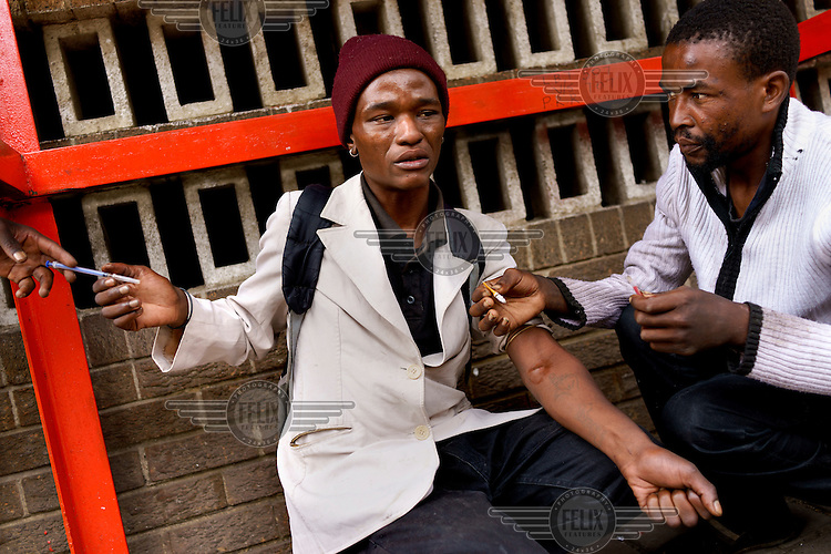 Thabo, a drug addict, reaches for his friend's needle to inject 'nyaope' on the streets of Hillbrow, a notorious inner-city neighbourhood of Johannesburg. <br /> Nyaope is a crude form of heroin reputedly cut with anything from anti-retrovirals to rat poison and pool cleaner. It is cheap (about R20/ $1.70 per 'round') and devastatingly addictive. It produces a brief high, but then leaves the user with vicious withdrawal symptoms.