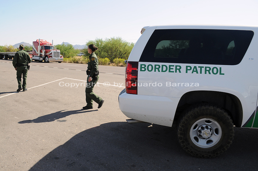 Nogales, Arizona - Two Border Patrol agents look toward the location of a permanent U.S. Customs and Border Protection (CBP) traffic checkpoint located on highway Interstate 19, north from Nogales and near the Town of Tubac, Arizona. Border Patrol checkpoints serve as inspection stations to detect illegal immigration and drug smuggling. Border Patrol agents assigned to fixed traffic checkpoints may stop a vehicle for brief questioning of its occupants. This checkpoint is part of the Border Patrol Tucson Sector. Photo by Eduardo © 2012