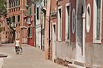 A local woman walks home with bags of groceries on Murano Island, the glass making island outside of Venice, Italy