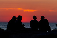People sit on the jetty after watching the sunset over the Vineyard Sound at Menemsha Beach in Chilmark, Massachusetts on Martha's Vineyard.