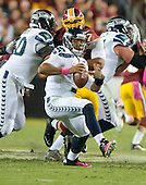 Seattle Seahawks quarterback Russell Wilson (3) eludes <br /> Washington Redskins right defensive end Jason Hatcher (97) in first quarter action at FedEx Field in Landover, Maryland on Monday, October 6, 2014.<br /> Credit: Ron Sachs / CNP