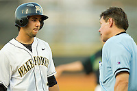 Carlos Lopez #3 of the Wake Forest Demon Deacons discusses a strike call with home plate umpire Gary Swanson during the game against the Charlotte 49ers at Gene Hooks Field on March 22, 2011 in Winston-Salem, North Carolina.  Photo by Brian Westerholt / Four Seam Images