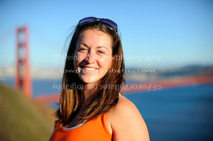A young woman poses in front of The Golden Gate Bridge for a portrait.