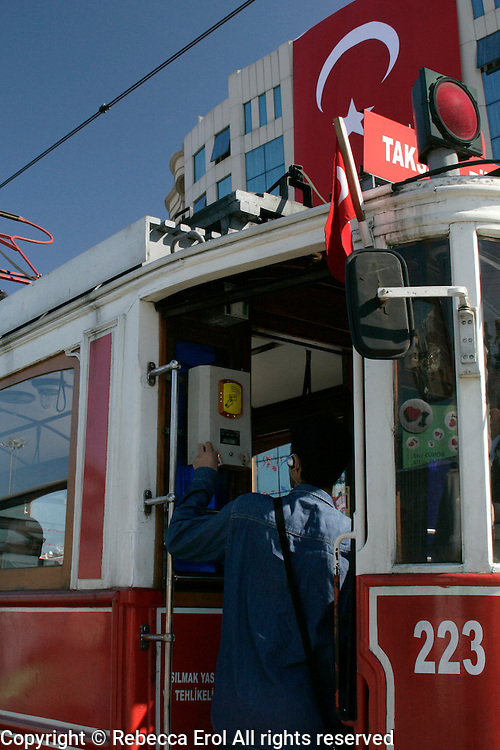 Turkish boy uses his akbil as he boards the tram on Taksim Square, Istanbul, Turkey