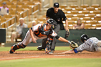Glendale Desert Dogs catcher Mike Ohlman (6) attempts to tag Pat Cantwell (15) sliding safely into home as umpire Shaun Lampe looks on during an Arizona Fall League game against the Surprise Saguaros on October 9, 2014 at Camelback Ranch in Phoenix, Arizona.  Surprise defeated Glendale 7-4.  (Mike Janes/Four Seam Images)