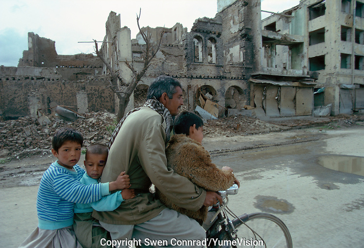 A father and is tree childrens on a bicycle driving up, what was the High Street of Kabul.The fight (1992 to 1995) between warlords Ahmad Shah Massoud of the Jamiat-e Islami and Gulbuddin Hekmatyar from the Hezb-e Islami, destroy one third of the Afghan capital.