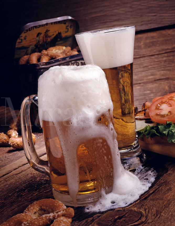 foamy mug of beer in front of a glass of beer on a rustic surface strewn with pretzels