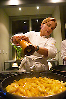 Dolly Irigoyen frying slices of apples in a frying pan, seasoning with pepper. The Dolly Irigoyen - famous chef and TV presenter - private restaurant, Buenos Aires Argentina, South America Espacio Dolli