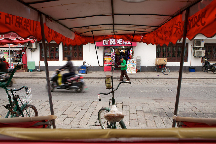Waiting for passengers, rickshaws stand ready to take tourists into Zhujiajiao Water Village outside Shanghai.