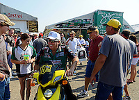 Sept. 22, 2012; Ennis, TX, USA: NHRA funny car driver John Force drives his scooter past fans in the pits during qualifying for the Fall Nationals at the Texas Motorplex. Mandatory Credit: Mark J. Rebilas-US PRESSWIRE