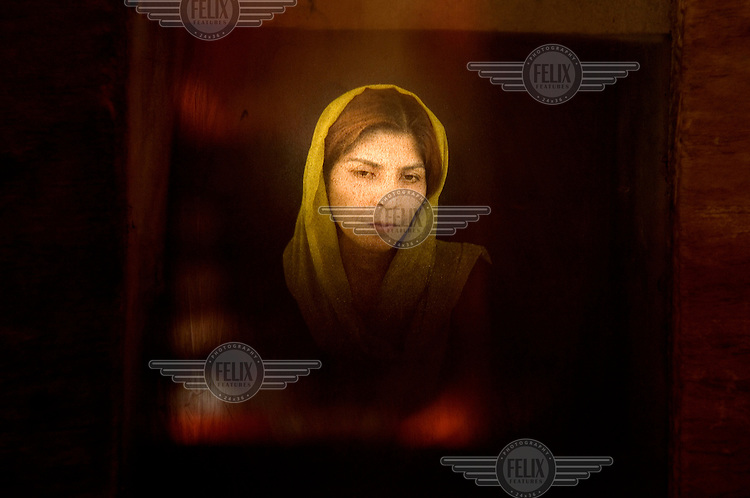A woman poses for a photo taken with an old Afghan box camera.