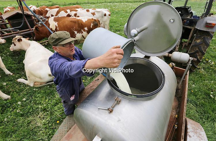 Foto: VidiPhoto<br /> <br /> OCHTEN - De ultieme vorm van weidegang donderdag. Niet alleen de koeien, maar ook de boer moet de wei in. Het is letterlijk een uitstervend ras; melkveehouders die hun koeien melken in het veld. Melkveehouder Kees Buis (63) uit Ochten doet dat al jaar en dag als zijn koeien buiten lopen. Om de 23 beesten te vangen, aan de weidewagen te binden en vervolgens met een installatie te melken, is hij iedere keer -tweemaal per dag- anderhalf uur zoet. De melk wordt vervolgens opgeslagen in een weidetank en naar de boerderij getransporteerd. Slechts een handjevol boeren werkt nog op deze ouderwetse manier.