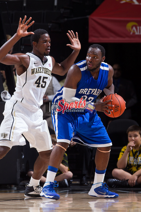 Darius Moose (23) of the Brevard Tornados is defended by Arnaud William Adala Moto (45) of the Wake Forest Demon Deacons at the LJVM Coliseum on November 1, 2013 in Winston-Salem, North Carolina.  The Demon Deacons defeated the Tornados 93-66. (Brian Westerholt/Sports On Film)