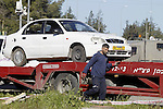 An Israeli policeman stands guard during the removal of a car used by a Palestinian woman who, the Israeli military said, rammed it into an Israeli soldier before she was shot dead by the Israeli troops, at a main junction near the Israeli settlement bloc, Gush Etzion in the West Bank March 4, 2016. Photo by Wisam Hashlamoun