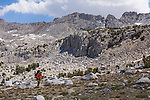 Woman backpacker hiking in rugged terrain in the High Sierra mountains near French Canyon and Pine Creek Pass.