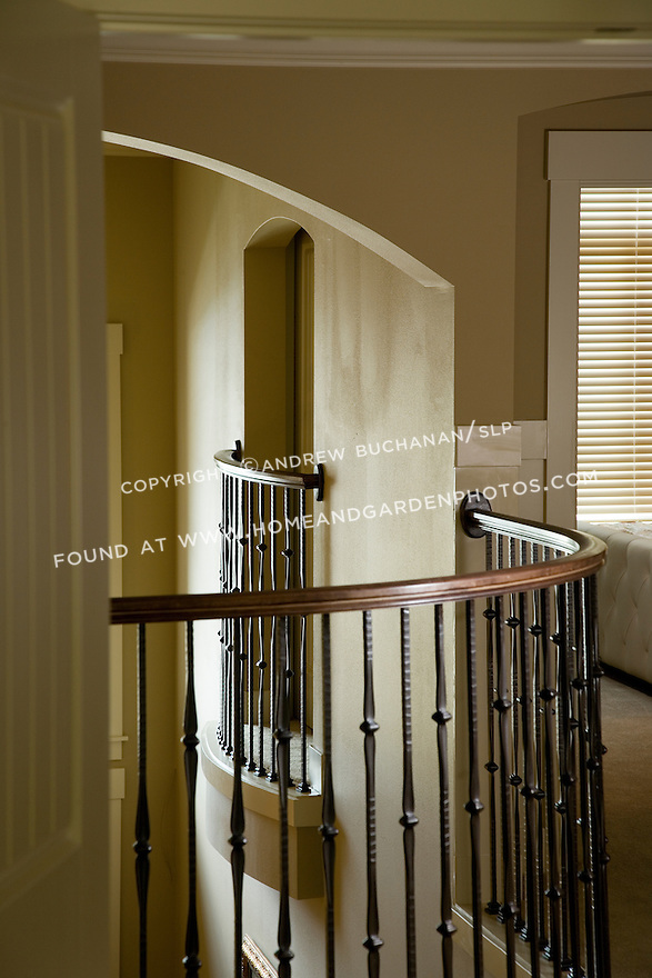 Light highlights the decorative, curved curving wrought iron ballusters posts supporting the hand rail in a detail shot of this upstairs balcony rail railing in a contemporary builder spec house.