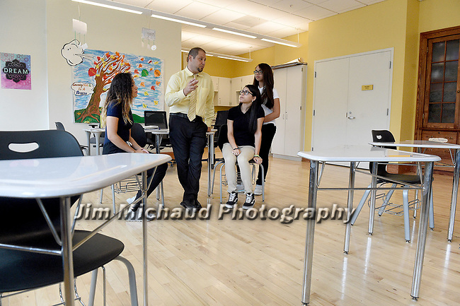 (09/18/17 Springfield MA) Thomas Mazza, principal of the Forest Park Middle School, chats with students Yeseliz Ortiz, Ariana Figueroa, right, and Xiomareliz Rivera, standing, Monday, Sept. 18, 2017, in Springfield. Herald Photo by Jim Michaud