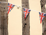 Union Jack flag bunting on ancient building, Debenham, Suffolk, England, UK