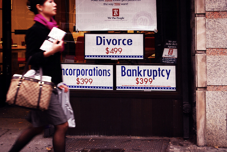 Advertising posters for a cheap divorce and bankruptcy in the window of a law agency. Manhattan, New York.