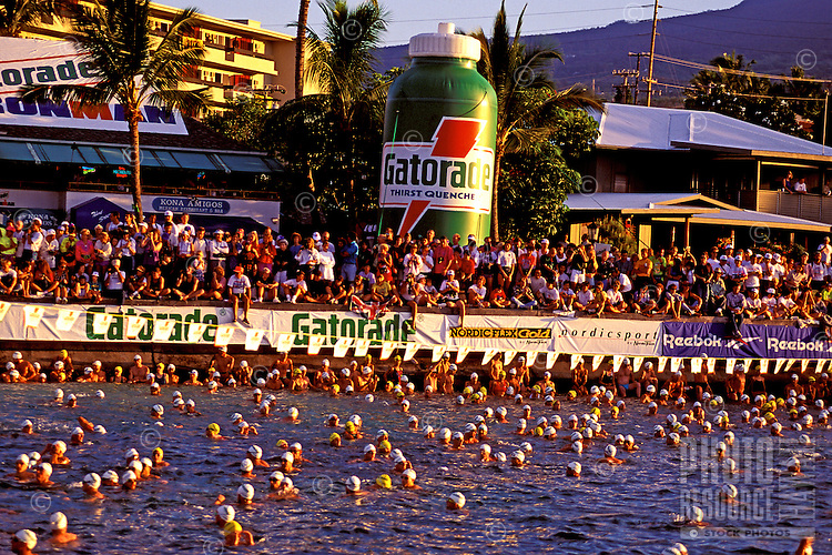 Swimmers gather in the water with spectators looking on at the annual Ironman Triatholon in Kailua-Kona on the Big island of Hawaii.