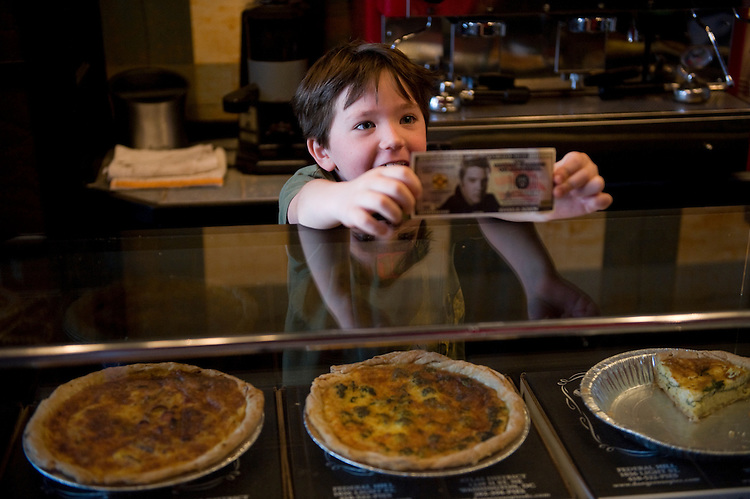 Waylon Henry, 7, son of Rodney Henry, co-owner of Dangerous Pies on H Street, NE, displays a fake dollar bill at the counter, April 5, 2010.