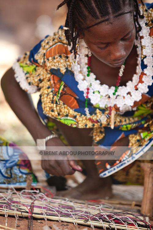 In the town of Djibo in northern Burkina Faso, a Fulani woman weaves a straw mat.  For these nomads, the mats are traditionally used to sit/sleep on (mattresses), as well as to make dry season houses.