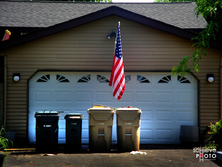 American flag above trash and recycling containers.