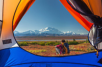 View of Denali and backpacker from inside the tent, autumn in Denali National Park, Alaska.