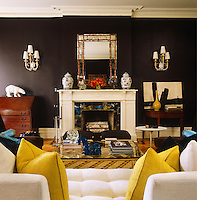 The aubergine walls in the living room are complimented by the accents of blue and yellow in the soft furnishings