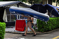 Switzerland. Canton Ticino. Tenero. Camping Campofelice. A man wearing a swimsuit carries on his head an inflatable boat. A campervan (or camper van), sometimes referred to as a camper, or a caravanette, is a self-propelled vehicle that provides both transport and sleeping accommodation. A motorhome (or motor coach is a type of self-propelled recreational vehicle (RV) which offers living accommodation combined with a vehicle engine. Motorhomes are part of the much larger associated group of mobile homes which includes caravans, also known as tourers, and static caravans. A caravan, travel trailer, camper or camper trailer is towed behind a road vehicle to provide a place to sleep which is more comfortable and protected than a tent. It provides the means for people to have their own home on a journey or a vacation. Campers are restricted to designated sites for which fees are payable. 20.07.2018 © 2018 Didier Ruef
