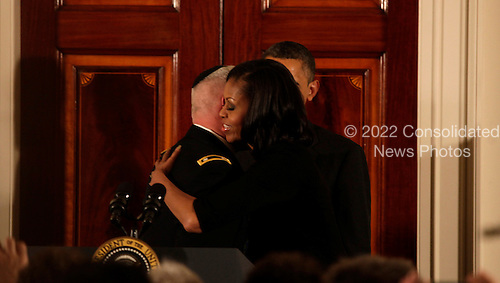 First lady Michele Obama greets Rabbi Larry Bazer, the Joint Forces Chaplain for the Massachusetts National Guard, while United States President Barack Obama watches at the end  of the Hanukkah Reception in the Grand Foyer of the White House  in Washington DC, on December 13, 2012..Credit: Aude Guerrucci / Pool via CNP
