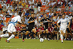 15 May 2004: Dema Kovalenko (21) tries to find a way through Shavar Thomas (left) and Alez Zotinca (23) in the first half while Ben Olsen (second from  right) makes an overlapping run. DC United defeated the Kansas City Wizards 1-0 at RFK Stadium in Washington, DC during a regular season Major League Soccer game..