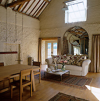 A large sofa and mirror at one end of the barn which has been converted into an open-plan living and dining space