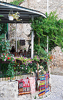 A restaurant with a display of colourful carpets for sale. The busy old market bazaar street Kujundziluk with lots of tourist craft and art shops and street merchants. Historic town of Mostar. Federation Bosne i Hercegovine. Bosnia Herzegovina, Europe.