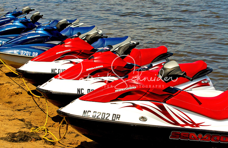 A line of Seadoo jet skies rest on the sand ready for ocean riding. Photo is part of a series of images taken at Pamlico Sea Base, a Boy Scouts of America High Adventure Camp located on the Pamlico River south of Washington, NC. The BSA Sea Base program is centered around sea kayaking treks on the North Carolina Outer Banks and sailing programs on the historic Pamlico River...Photography by: Patrick Schneider Photo.com
