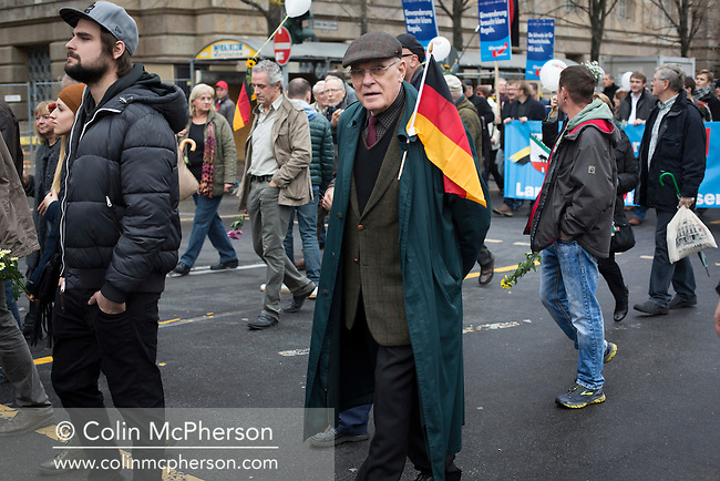 An elderly man with a German flag marching through the streets of Berlin during a demonstration by the Alternative für Deutschland (AfD) political party. Around 5000 supporters of the AfD took part in the march and rally calling on German Chancellor Angela Merkel to halt the influx of refugees into the country. Around one million refugees from the Middle East and north Africa arrived in Germany during 2015, 50,000 of whom came to Berlin.