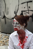 Female participating in the Zombi walk in prague, wearing a white shirt with a note pinned to her chest with a name on it and fake blood in her face and on her chest.