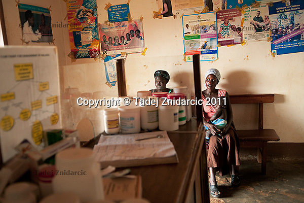 Teo Nakatudde (L) and Agnes Nakazibwe (R) sit in the waiting room of Bbanda Health Center, Mityana district, Uganda. In addition to government health centers there are also private health centers that many people attend since they prefer them over government health centers.