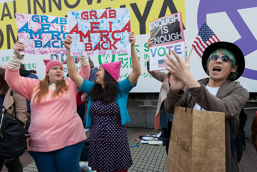A Japanese man joins protesters at the Vote Out the Scandal rally at Hachiko Square, Shibuya, Tokyo, Japan. Sunday November 5th 2017. Timed to coincide with President Trumps visit to Japan, About 120 Americans living in Japan and some local Japanese  protested together from 2pm to 4pm to encourage US citizens to register to vote in future elections and call on the US government to honour it responsibilities to the American people,.