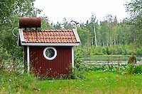 Traditional style Swedish wooden painted house. A small water tank on the roof to make running water. Smaland region. Sweden, Europe.