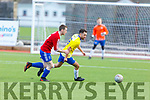 Ray Walsh of Classic FC and CG Killarney's Andrew O'Sullivan keep the eyes on the ball, in the Denny League game in Mounthawk Park on Sunday.
