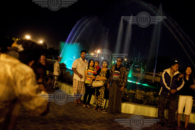 Visitors pose for souvenir photos in front of a water park fountain show in Naypyitaw, the new capital of Burma (Myanmar) since November 2005.