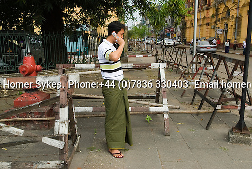 Man on a rare mobile telephone and security baricade around a government building Yangon Myanmar ( Rangoon Burma ) South east ~asia 2006.