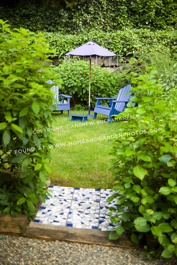 Two blue-painted Adirondack chairs sit under a blue umbrella on a small pocket of grassy lawn, hidden behind a hydrangea hedge in this small residential garden.
